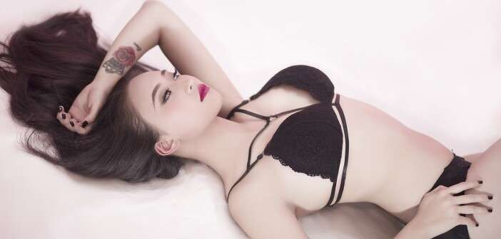 Brunette in black lingerie posing while lying down