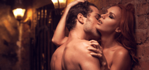man kissing woman's neck while up against the wall