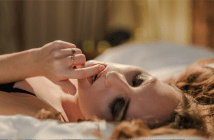 woman in bed with eyes closed with finger in her mouth